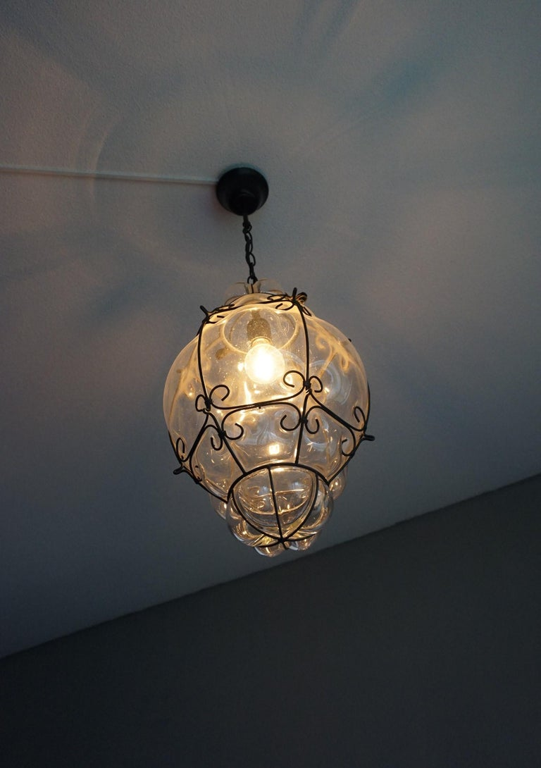 Italian craftsmanship pendant.   This stylish single light pendant is beautiful in shape and the mouth blown, transparant glass is in excellent condition. It comes with a blackened metal chain and ditto canopy and the bulb can easily be replaced by