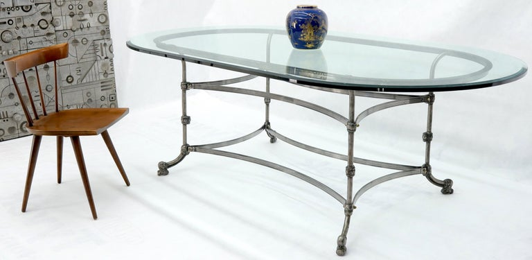 Decorative large forged metal base thick glass racetrack oval shape top dining conference table. Heavy and sturdy nice looking dining table.