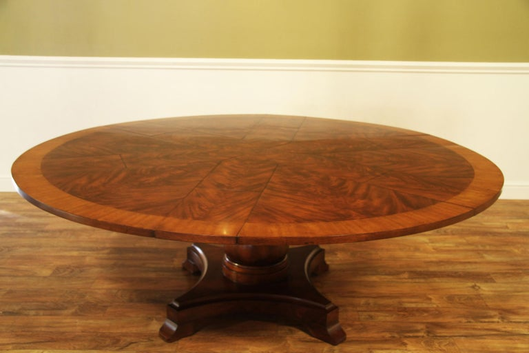 This is large round Jupe traditional mahogany dining table by Leighton Hall. It features a radial cut field of West African swirly crotch mahogany and a border of satinwood. The Jupe design allows the leaves to be self-storing inside the table. The