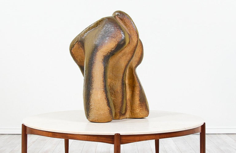 Modern abstract ceramic sculpture designed and manufactured in the United States, circa 1960s. This large sculpture is made of glazed ceramic showing earthy tones and organic forms, creating a unique asymmetrical shape. The surface shows a grainy