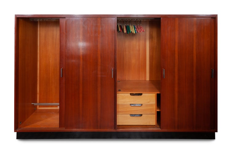 Vintage midcentury wardrobe by Alfred Hendrickx for Belform Belgium. Beautiful warm exotic wood frame on floating black platform base. Silver metal handles. The sliding doors open to reveal generous hanging space, two adjustable shelves and three