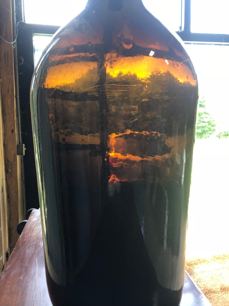 A large amber glass hand blown wine bottle, circa 1850.