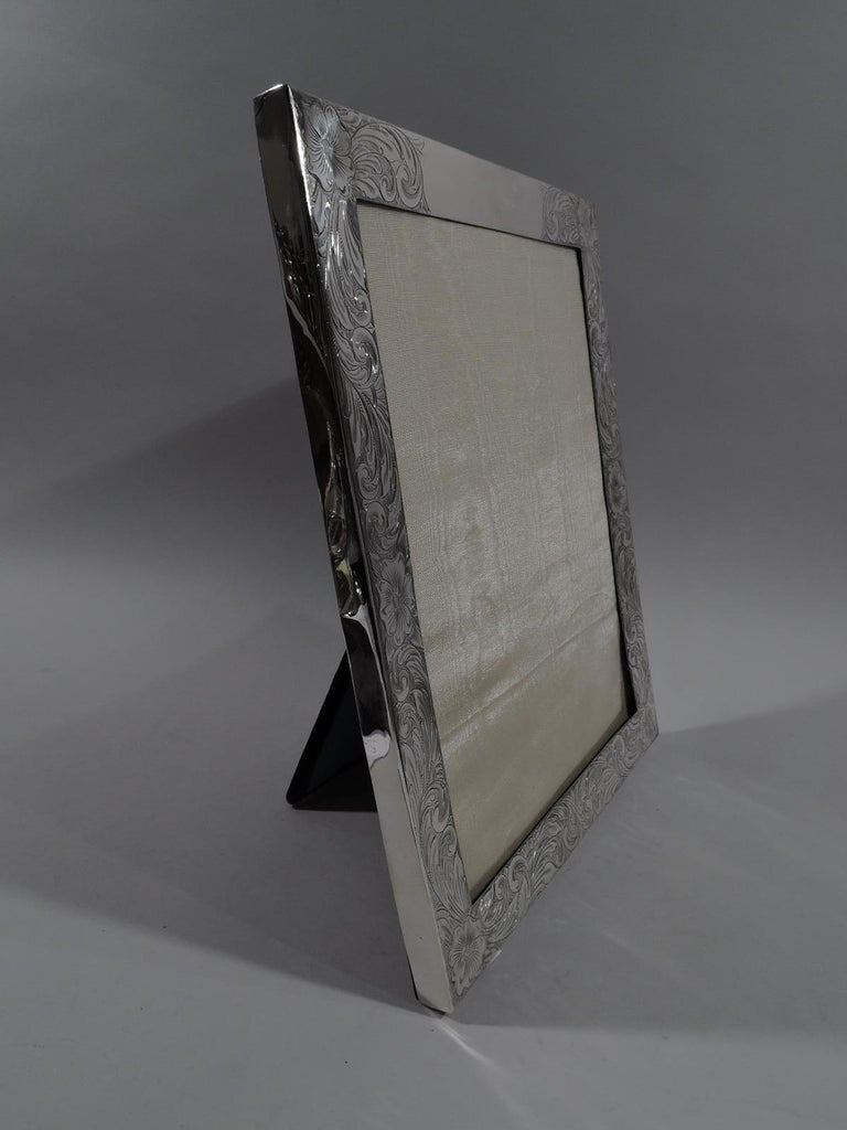 Large American Art Nouveau sterling silver picture frame. Rectangular window in flat surround engraved dense and dynamic scrolls and flowers; sides plain. Top rail has shaped cartouche (vacant). With glass, silk lining, and velvet back and hinged