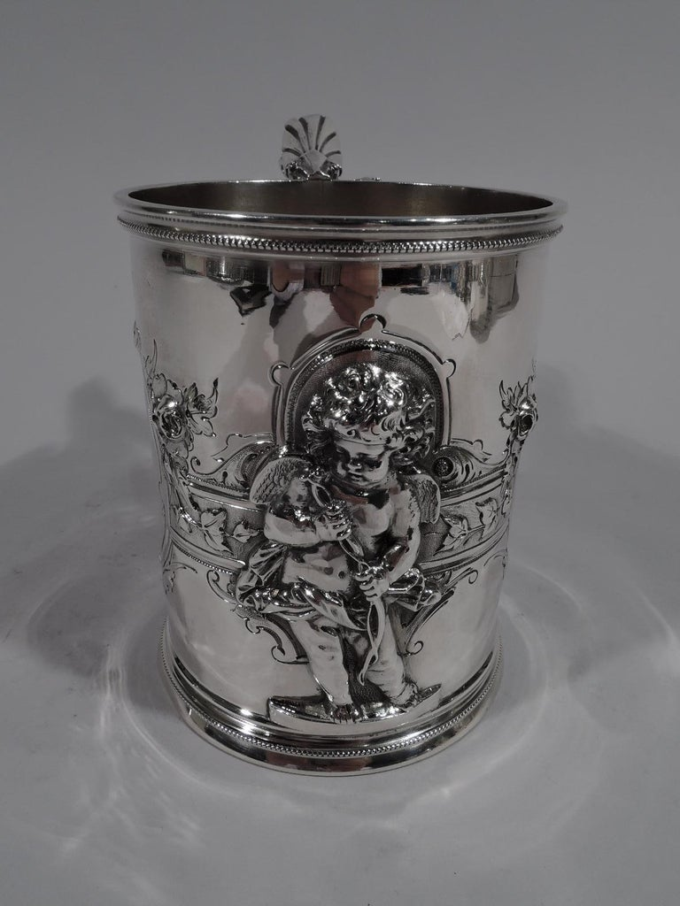 Large American classical coin silver baby cup. Made by Wood & Hughes in New York, ca 1860. Upward tapering sides with skirted foot and scroll-bracket handle. Jowly, tousled-haired contrapposto cherub applied to front. Two oval frames and one small