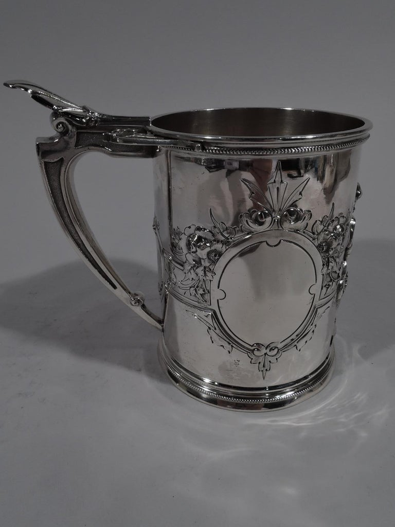 Large American Classical coin silver baby cup. Made by Wood & Hughes in New York, circa 1860. Upward tapering sides with skirted foot and scroll-bracket handle. Jowly, tousled-haired contrapposto cherub applied to front. Two oval frames and one