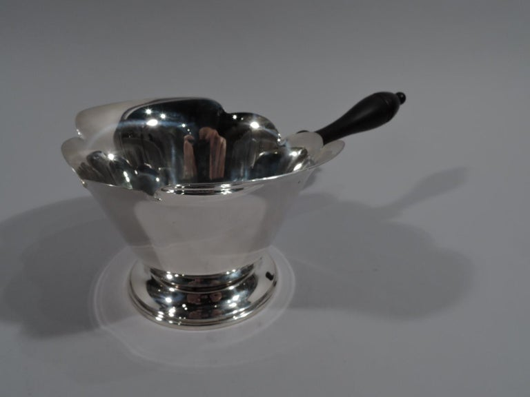 Large American Modern sterling silver pipkin. Conical bowl with scalloped rim and spread foot. Stained-wood baluster handle. Fully marked including maker's stamp comprising letter A in triangle, and no. 403.   Overall dimensions: H 3 1/2 x W 10 x