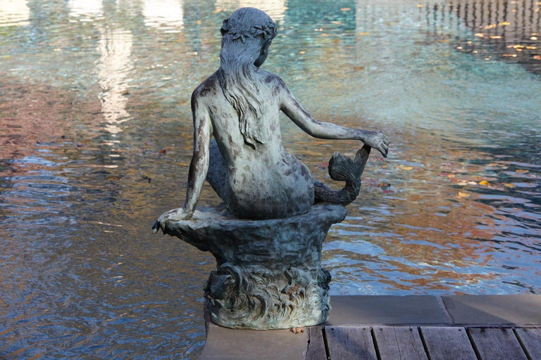 A beautifully detailed bronze water garden/fountain statue of a mermaid sitting on a stone, circa 1940s. The statue has a wonderful, lovely green patina. The statue is piped.