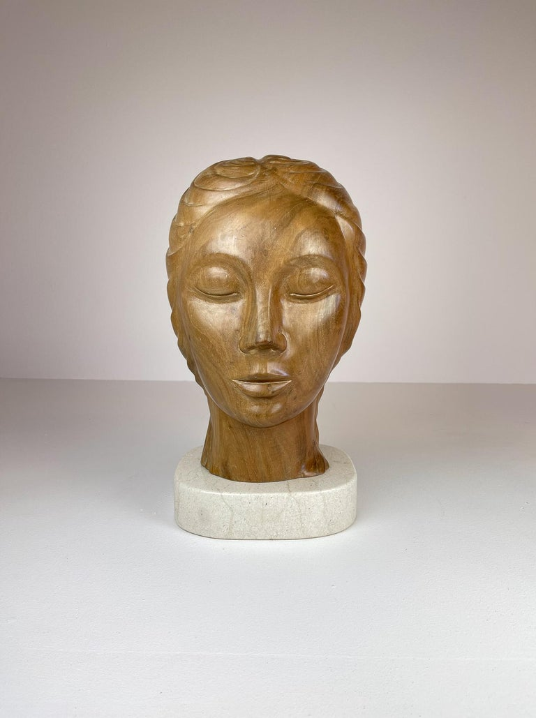This sculpture is made in mahogany and is incredibly well sculptured. The solid mahogany piece is placed upon a stone. It is very heavy and large. The craftsmanship to this piece is out of the ordinary with its carvings to create a living and