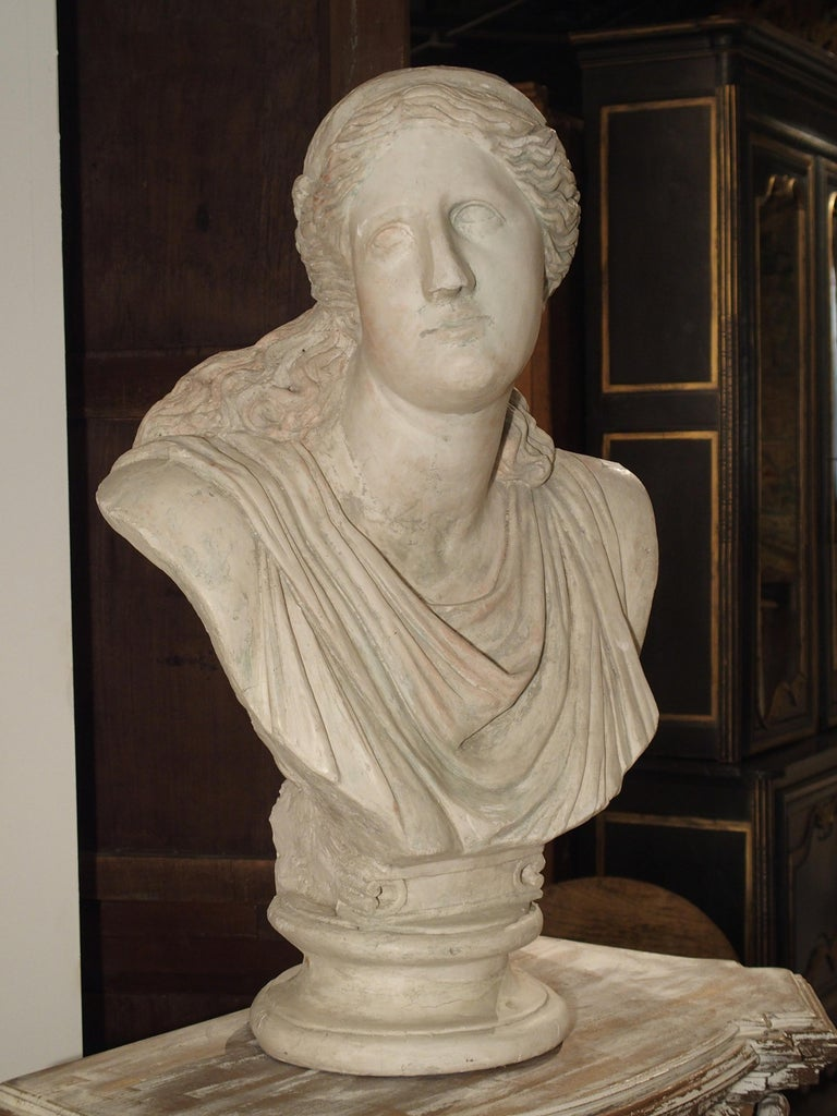 This large scale plaster bust depicts Niobe of Greek mythology. She is looking to the side, gazing slightly upward, and she wears a draped top with her long curly hair falling down upon her shoulders. This is an Italian work, circa 1880, based on
