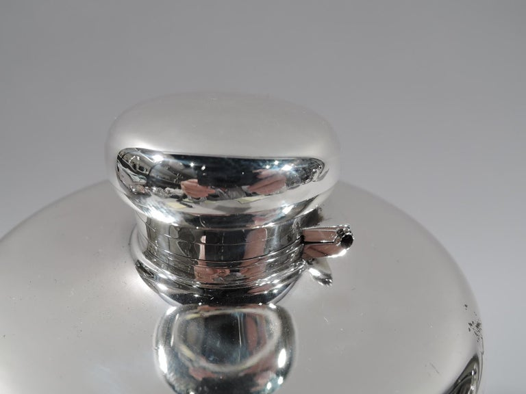 Large and unusual sterling silver flask. Made by Tiffany & Co. in New York, circa 1910. Truncated cone; gently curved and overhanging top with hinged and cork-lined bun cover. A big game-era vessel for passing around the campfire. Wide hand span