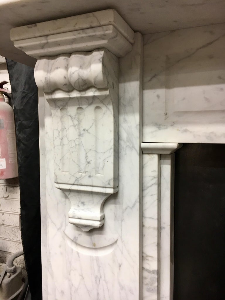 A large and splendid mid-Victorian antique 19th century Carrara marble fireplace surround, of superb quality and colour. A wide scalloped shelf sits above a panelled frieze displaying great veining, flanked by well carved bobbin & fluted corbels