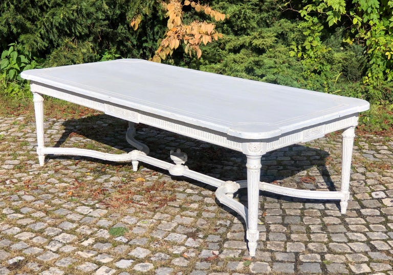 This exceptional, antique Gustavian style painted dining room table was crafted in Sweden, circa 1870. The Gustavian style was influenced by the French Louis XVI style. The table has a wonderful painted patina finish, a carved apron, tapered legs,
