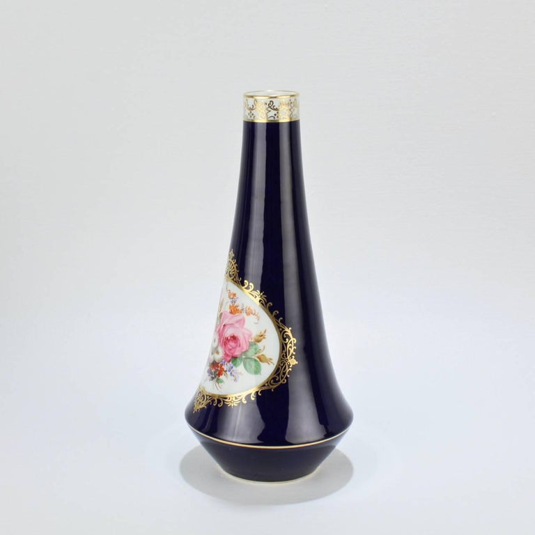 A fine Meissen porcelain vase with a cobalt blue ground, floral spray in a central cartouche, and gilding throughout. 