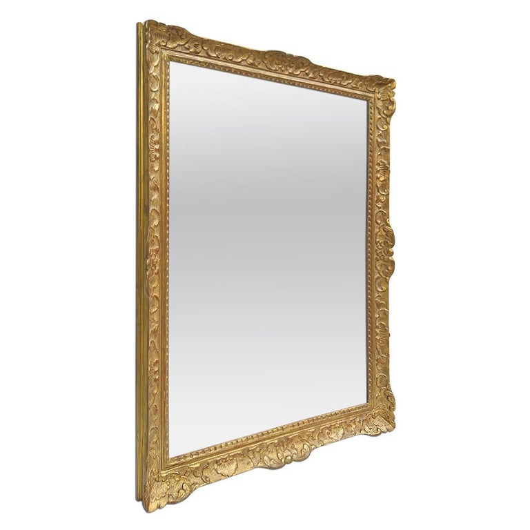 Large antique French mirror of Louis XIV style, circa 1965. Antique carved gilt wood frame (width: 8 cm / 3.14 in.) with French decor Louis XIV style. Gilding to the patinated gold leaf. Modern glass mirror. Antique wood back.