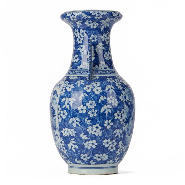 A large antique Chinese Qing porcelain twin handled bulbous vase hand painted with panels with birds set amidst flowering plants to two sides within a surround of flowering shrubs within a blue cracked ice ground. The vase has a rounded bowl shaped