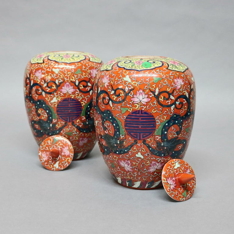 A pair of large and antique Chinese porcelain lidded urns offer hand enameled decoration with all-over scroll decoration with central