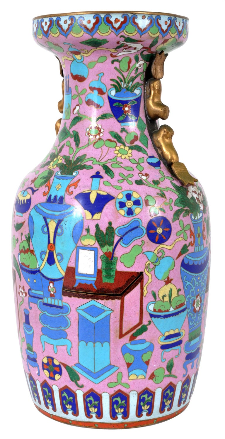 A large and fine antique Chinese Cloisonné vase, circa 1920. The vase decorated with lappets to the top and profusely decorated with vases, scholars objects, furniture and flowering urns as well as other geometric devices. The vase having a band of