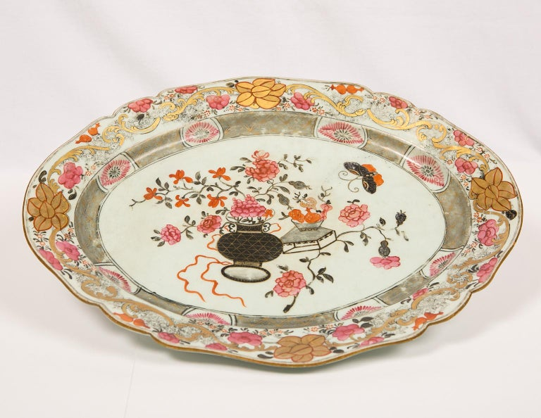 We are pleased to offer this large Chinese porcelain platter which is decorated with vibrant floral patterns in a beautiful palette of pink, gray, black and gold. Made in the first half of the 19th century, it is painted in the center showing a