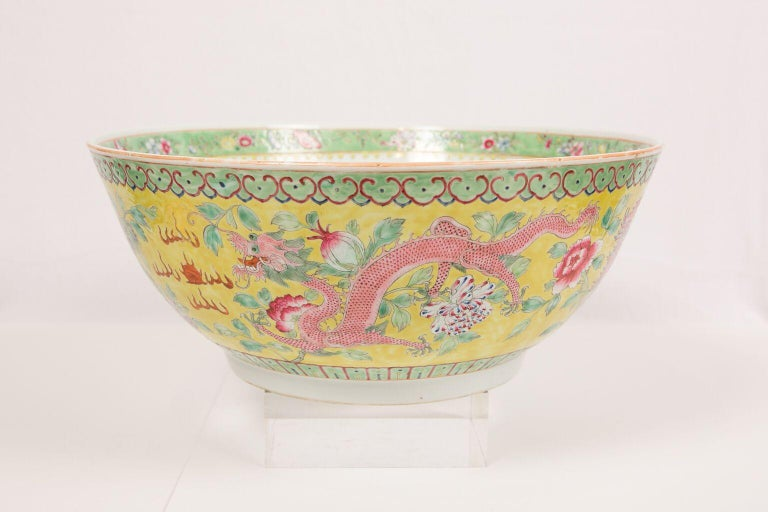 WHY WE LOVE IT: Dragons and Phoenixes and Fabulous Colors!  We are delighted to offer this large and beautiful Chinese porcelain punch bowl. Decorated in Famille Rose the exterior of the bowl shows a pair of vigorous dragons, and a pair of splendid