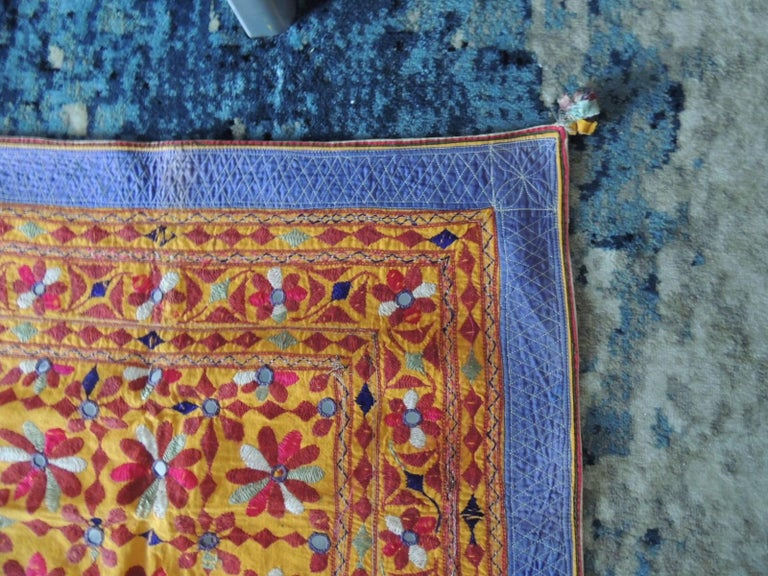 Large antique embroidered panel with floral pattern. Indian colorful wall hanging from Gujarat land of Rajasthan. Embroidery and inset mirror work all around and cotton quilted border. Hanging loops and small decorative tassel on corners. Size: