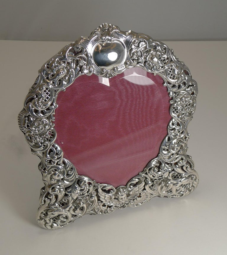 A grand large heart shaped photograph frame made from English sterling silver with intricate pierced or reticulated work incorporating Dolphins on either