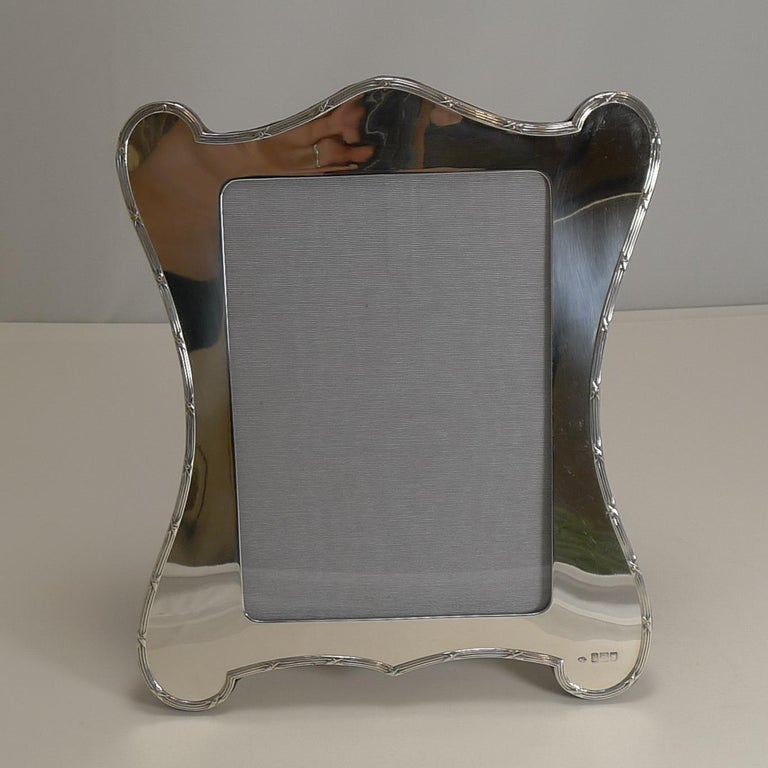 A fabulous large Edwardian photograph frame, wonderful quality and condition.  Made from English sterling silver, this shaped frame has an understated elegance with a simple ribbon and reed border showcasing the shape. The silver is fully