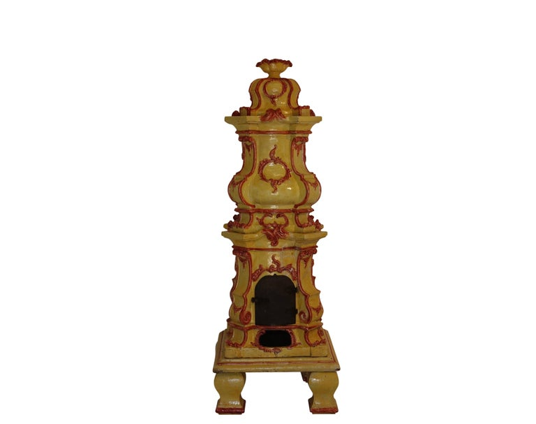 Ornate finial above serpentine and bombe sections modeled with scrolling foliage rocaille cartouches and ornamentation. Hinged cast iron door on firebox resting upon flat plate and four block feet. Stove is in six sections.