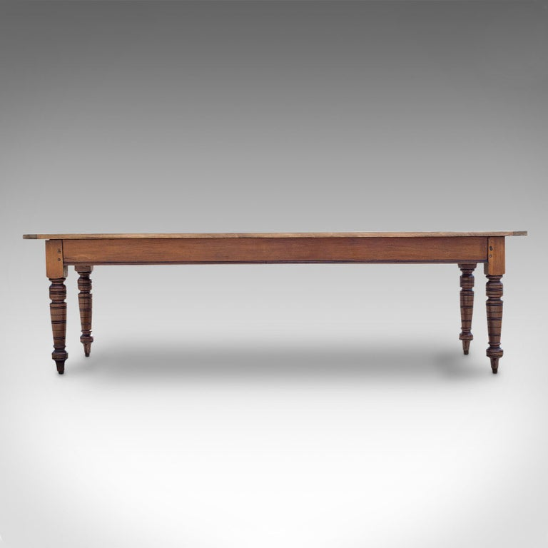 This is a large antique farmhouse table. An English, mahogany and pine dining or kitchen table for 8-10 people, dating to the Victorian period and later, circa 1900.  Generous proportions of 8' 6