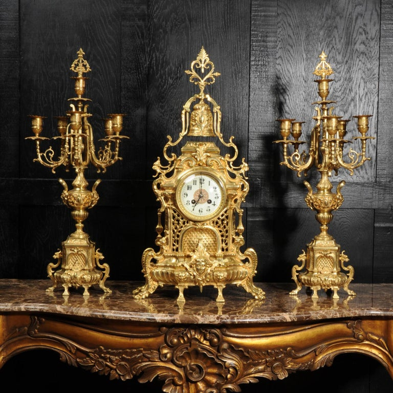 A large and impressive original antique French Baroque clock set, beautifully made in gilt bronze. It is heavily and crisply modelled with lions masks, hairy paw feet, flowing foliage and surmounted by a bell. The front of the clock is modelled as a