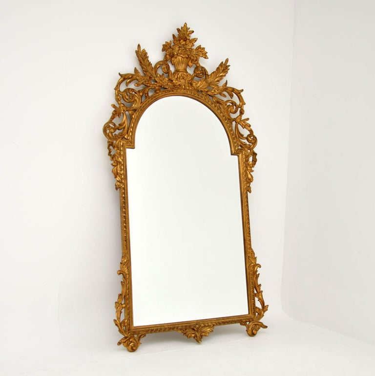 A large and impressive antique carved gilt wood mirror, which I would say is French, dating from around the 1950's period.  It is beautifully made and has a stunning design. There is intricate floral carving throughout, this is beautifully gilded