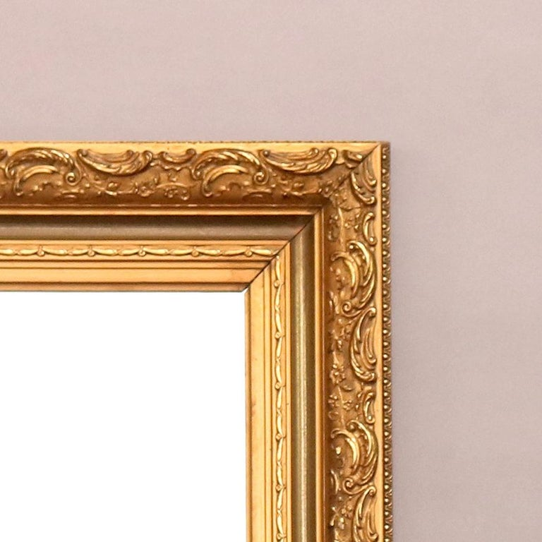 A large and antique French wall mirror features foliate and scroll decorated giltwood frame, c1920  Measures - 37.25