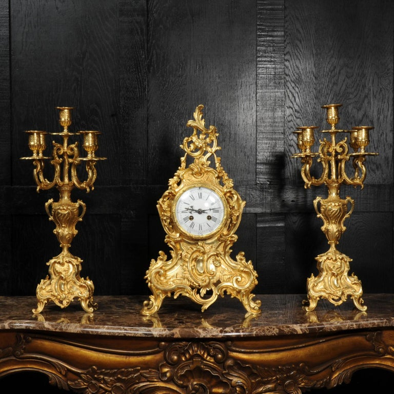 A stunning and large original antique French gilded bronze clock set, circa 1870. It is of the most beautiful Rococo style, waisted case decorated with 'C' scrolls, acanthus leaves and floral swags. Candelabra have 4 elaborate acanthus arms held