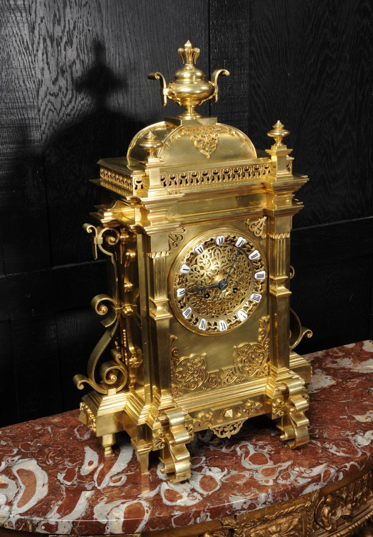 A very large antique French clock in the Gothic style. It is of exquisite quality in gilt bronze, architectural in design with a domed top, blind fret work decoration and scrolling brackets to the sides. The detail is beautifully finished and well