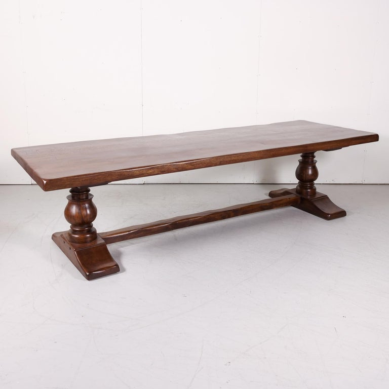 Large antique French monastery trestle table handcrafted of solid oak in Normandy, circa early 1900s, Supported on an oak base by a pair of hand carved baluster legs, each resting on a carved