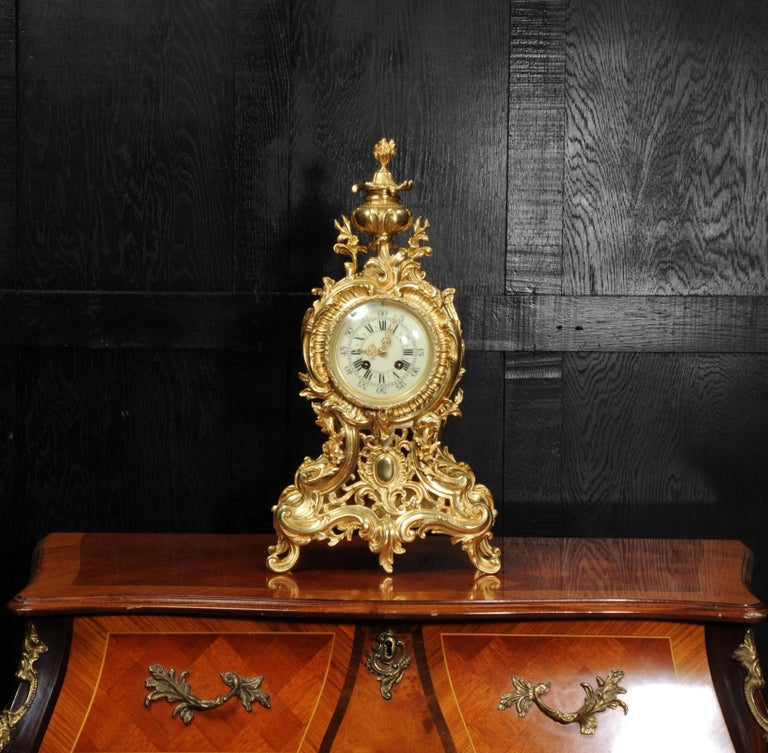 A large, superb and very decorative original antique French clock dating from circa 1900. It is boldly modelled in the Rococo style in finely gilded bronze. Waisted shaped case, decorated profusely with acanthus leaves and 'C' scrolls. The front is