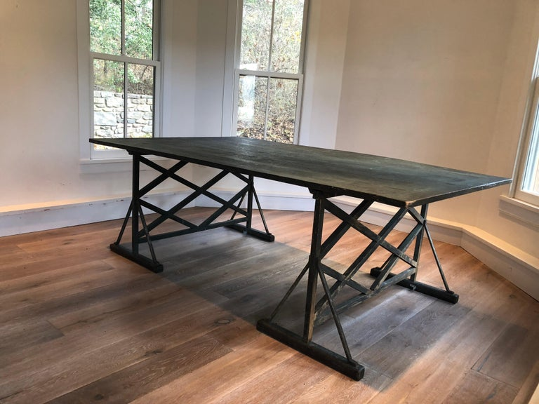 A large green painted antique French trestle table. Wide Plank top with trellis design legs.