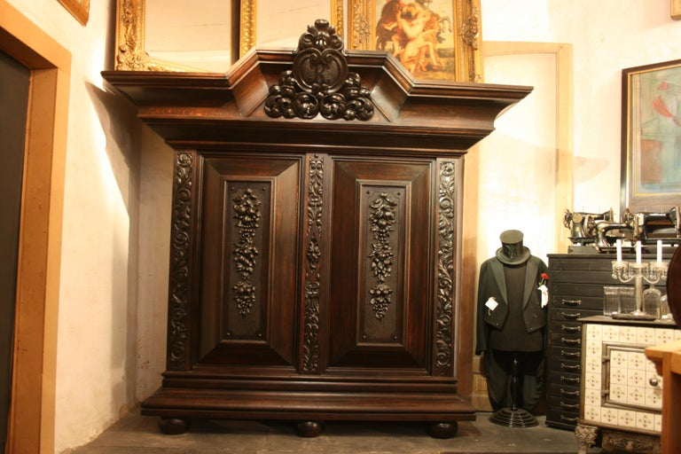 Original old German cushion cabinet or wardrobe / cupboard made of solid oak, from the period of 1880-1920 - Historicism. Inside equipped with shelves. In the enormously big crown a big K initial is carved. Can be dismantled for transport in several