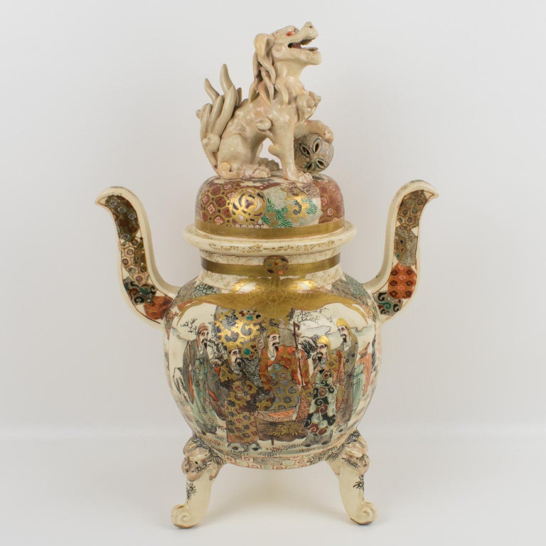 Beautiful large Japanese Meiji period (1868-1912) Satsuma porcelain covered vase or urn. The lidded jar is richly decorated with enamel and hand-painted Lohan scenes with gilt accents and has upturned handles and a lid with a Foo dog or dragon