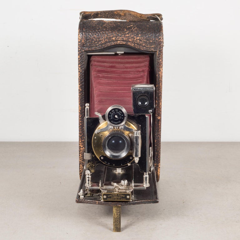 About  This is an original large Eastman Kodak No. 3A folding camera with red bellows. The body is wrapped in leather with chrome and brass accents. The camera folds to 2 inches. This piece has retained its original finish with minor structurally