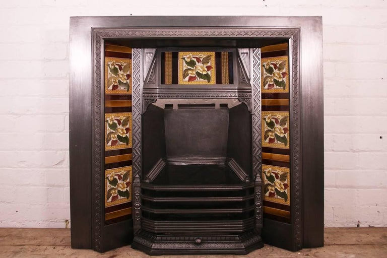 Large Antique late Victorian cast iron and tiled grate with a tiled canopy, circa 1890. Pictured with a set of original fireplace tiles, priced separately.   This grate has been finished the traditional black grate polish, leaving a gun metal /