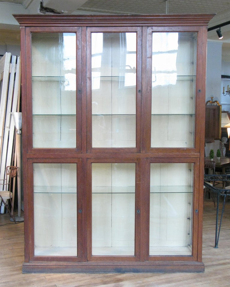 A very handsome antique late 19th century display cabinet with an oak case and glass doors and side lights. The interior back in its original pale cream color, and with four full width glass shelves.