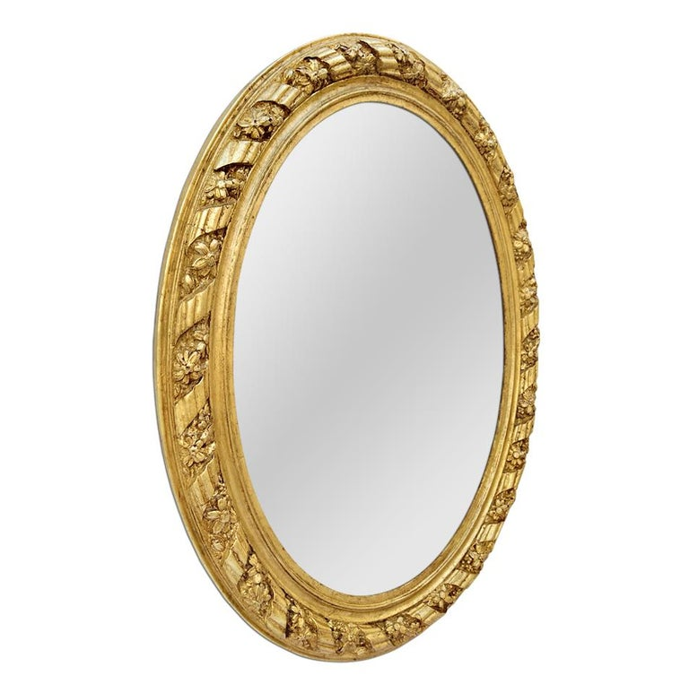 Antique oval mirror giltwood decorated with stylized ribbons and daisy flowers. Re-gilding to the leaf patinated. Modern glass mirror. Antique wood back. Antique frame width 7 cm / 2.75 in.