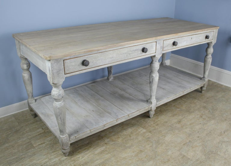 A fabulous prep or draper's table, newly painted for a distressed look. The top has been bleached for a clean appearance. The two wide drawers open and close easily and snugly. This can stand on it's own as a room divider or work table, or would be
