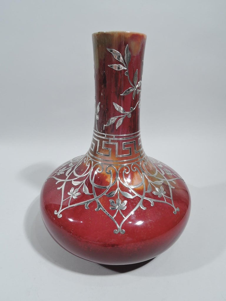 Large vase with engraved overlay, ca 1910. Wide bellied bowl and tall upward tapering cylindrical neck. Overlay in form of overlapping scrolled frames inset with stem flowers, and leafing branches and fretwork border. Red flambé ground with