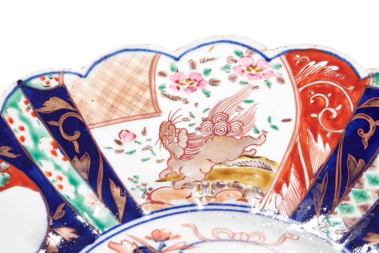 This is a large 19th century antique scalloped edge Japanese Imari porcelain dish with central jardinière of flowers and outer panels of kylin dogs. It is in perfect condition.