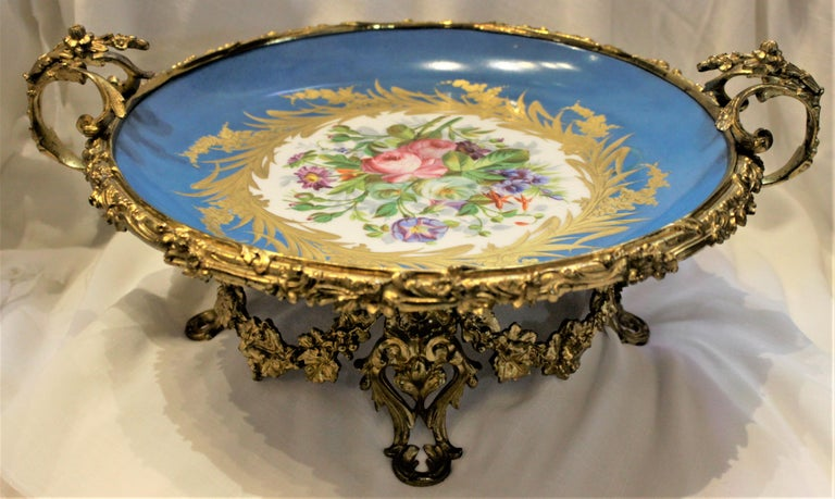 This antique Victorian centerpiece or pedestal bowl is unmarked, but believed to have originated from France in circa 1880 and done in the Sevres style. The bowl is done in a bright turquoise ground with a large hand-painted floral medallion