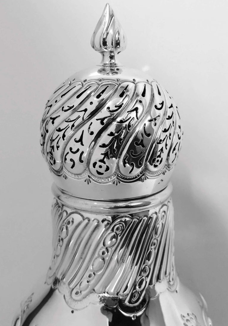 Large antique silver sugar caster, London 1899, William Gibson. The caster on pedestal base rising to tapered baluster body all with lobate swirl embossed design surround, the detachable large bulbous cover, swirl lobate pierced surround with flame