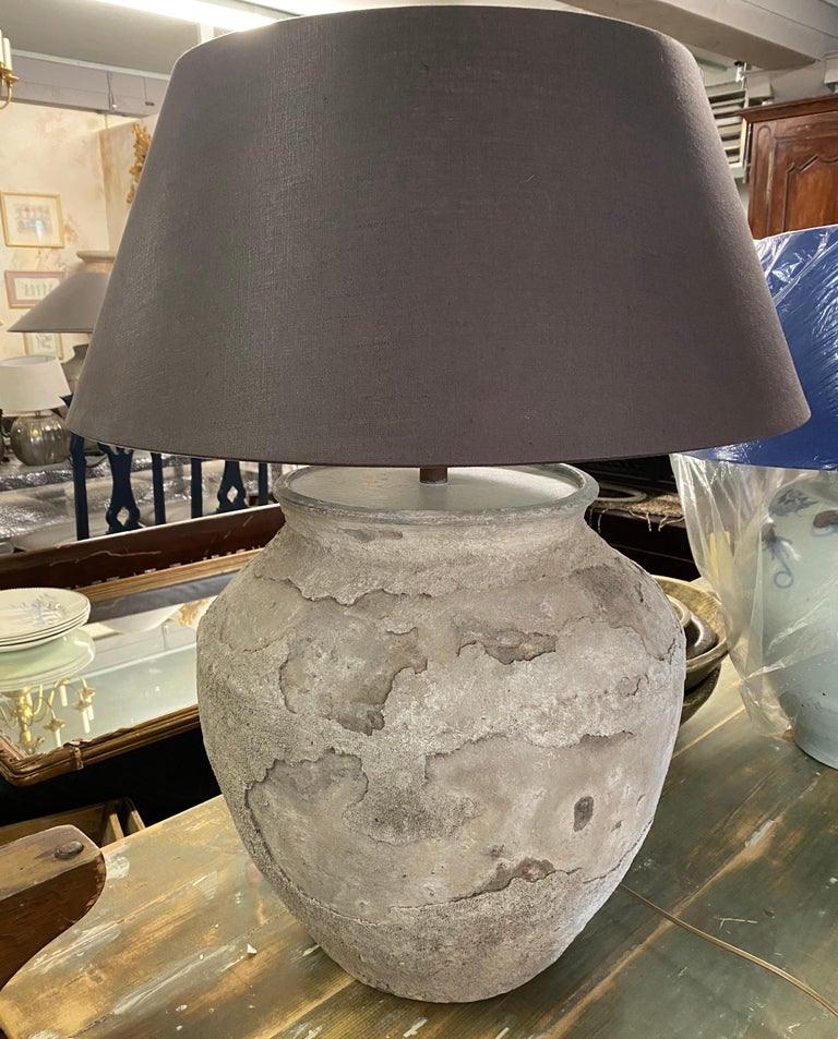 Impressive large rustic organic Chinese unglazed terracotta storage jar that has been made into a table lamp. The vase has beautiful aged patina from being buried perhaps for centuries. Handmade drum shape Belgium linen lampshade included.