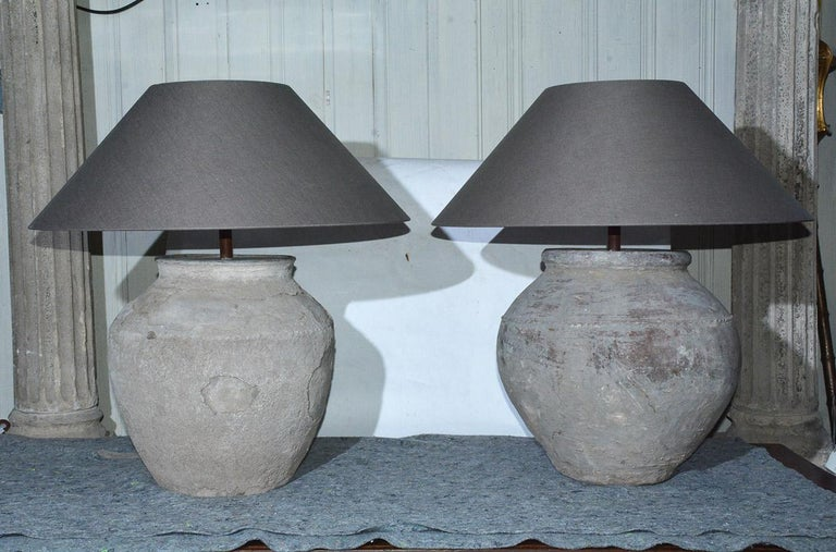 Two similar early large rustic organic Chinese unglazed terracotta storage jars that has been mounted as table lamps. The vases have beautiful aged patina from being buried perhaps for centuries. Handmade Belgium linen coolie shape lampshades