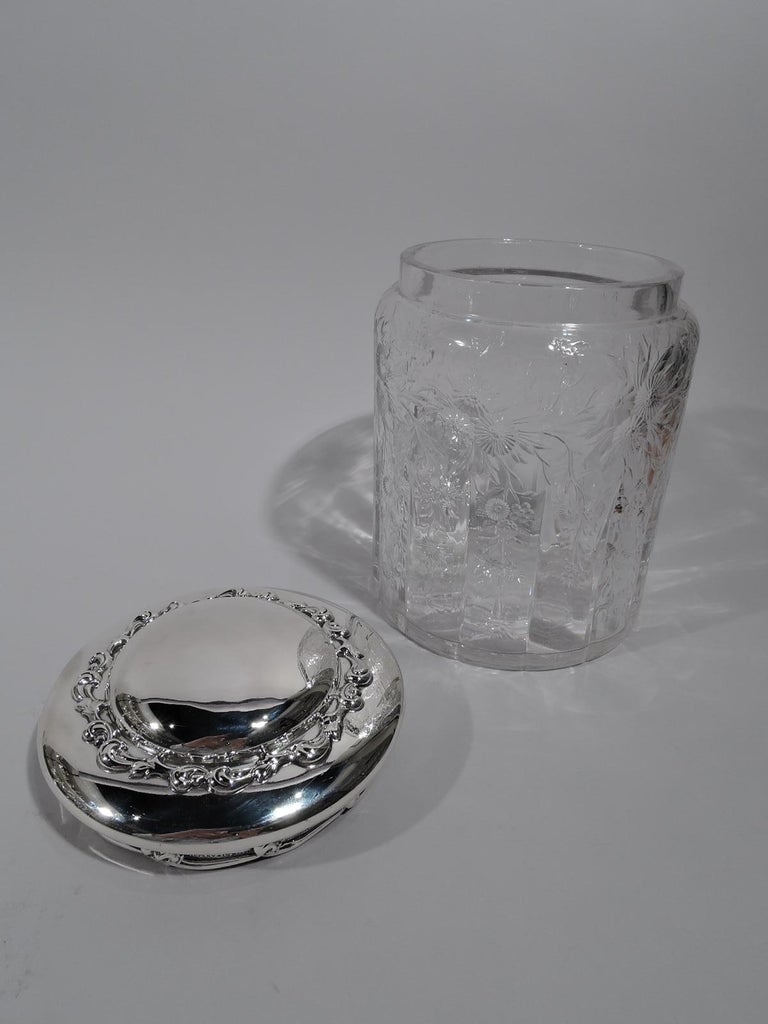 Large Art Nouveau glass jar with sterling silver cover. Made by Tiffany & Co. in New York. Jar has curved shoulders, short neck, and lobed base. Dense etched ornament in form of flowering branch with pendant offshoots dangling between half flutes.